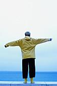 Allein, Alleine, Außen, Blau, Eine Person, Eins, Erwachsene, Erwachsener, Farbe, Frau, Frauen, Frauen (nur), Freizeit, Ganzkörper, Ganzkörperaufnahme, Horizont, Horizonte, Kurzes Haar, kurzhaarig, Mantel, Mäntel, Meer, Mensch, Menschen, Mit offenen Armen