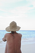 Adult, Adults, Alone, Back view, Bare, Beach, Beaches, Calm, Calmness, Chill out, Chilling out, Color, Colour, Contemporary, Daytime, Exterior, Female, Hat, Hats, Headgear, Holiday, Holidays, Horizon, Horizons, Human, Leisure, Medium-shot, Naked, Nude, N