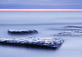 Limestone rocks in waters edge. Byrums Raukar at Öland Island in Kalmar Sound, Sweden.