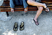 Adult, Adults, Anonymous, Barefeet, Barefoot, Bench, Benches, Color, Colour, Companion, Companions, Contemporary, Daytime, Exterior, Female, Footgear, Footwear, Ground, Grounds, Horizontal, Human, Leg, Legs, Leisure, Mate, Mates, Outdoor, Outdoors, Outsi