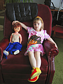 A three year girl with a dolly sits in her grandfather s chair during a visit.