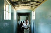 A nurse walks the hallway from the Howard Hospital Emergency to the Male Ward. The eighty year old salvation Army operated facility sometimes shows its age. The Hospital is located in northern Zimbabwe.