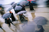 activity, blurred motion, business, businessman, businesspeople, city, Color image, contemporary, day, executive, horizontal, human, hurry, manager, motion, moving, occupation, outdoor, passer-by, pedestrian, people, profession, rain, rainy, rush, rushed,