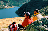 Hikers contemplating the landscape in Neouvielle Natural Park. French Pyrenees.