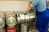 Worker transporting beer barrels to restaurant. Munich, Germany