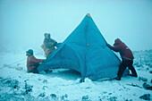 Abenteuersport, Aktivität, Außen, Campingplatz, Campingplätze, Drei, Drei Personen, Erwachsene, Erwachsener, Farbe, Ganzkörper, Ganzkörperaufnahme, Halten, Horizontal, Kalt, Kälte, Kraft, Kräftig, Mensch, Menschen, Schnee, Schneebedeckt, schneebedeckt, S