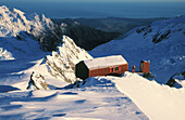 Skier and centennial hut at Franz Josef Glacier. Westland NP. South Island. New Zealand