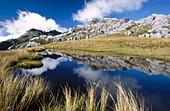 Tramper beside tarn on Mt. Owen. Eroded limestone landscape. Kahurangi NP. New Zealand