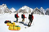 Skiers reach Concordia with K2 behind, Baltoro and Godwin-Austin Glaciers junction. Karakoram mountains, Pakistan