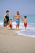 Mature couple with grandchildren walking at the beach, Florida, USA