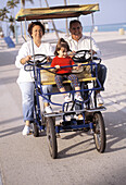 Mature couple with granddaughter riding a four wheel bike at the beach