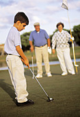 Boy playing golf with his grandparents