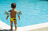 Infant boy standing by a pool