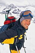 Young man carrrying climbing rope and ice axe on a ski tour, Ice climbing, Winter Sports, Sports, Stubai Alps, Tyrol, Austria