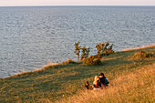 A couple sitting on a cliff at the Northern coast, Panga Pank, island Saaremaa, Estonia