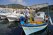 Two men working on a boat in Gaios harbour, Paxos, Ionian Islands, Greece