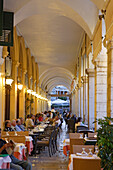 People sitting in cafes under the arcades of Liston, Corfu, Ionian Islands, Greece