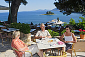 People sitting on the terrace of Cafe Kanoni, Corfu, Ionian Islands, Greece