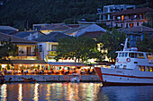 People sitting in a tavern at the harbour of Vasiliki in the evening, Lefkada, Ionische Inseln, Greece