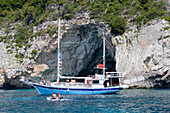 Paxos, people driving boats in front of caves on the West coast, Ionian Islands, Greece