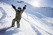 Boy skiing rising arms up, skiing region Sonnenkopf, Vorarlberg, Austria