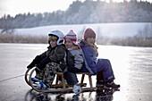Children sitting on sledge on frozen lake Buchsee, Munsing, Bavaria, Germany