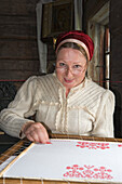 Woman in traditional Karelian dress doing embroidery in the open air museum on Kizhi island on Lake Onega, Karalia, Russia