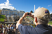 Man taking a photograph of the Grand Cascade in the park of Peterhof Palace, St. Petersburg, Russia
