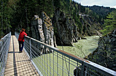 Woman on suspension bridge over Tiroler Ache, Entenlochklamm, Klobenstein, Chiemgau Alps, Tyrol, Austria