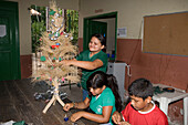 Children decorating a Christmas Tree in the school classroom, Combo Island, near Belem, Para, Brazil, South America
