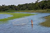 Fisherman throws out fishing net on Rio Tapajos, Near Santarem, Para, Brazil, South America