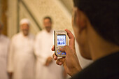 Man taking a photograph of friends with his mobile phone, Mobile Phone Snapshot in Umayyad Mosque, Damascus, Syria, Asia