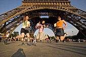 Japanese girls jumping in front of the Eiffel Tower, Paris, France, Europe