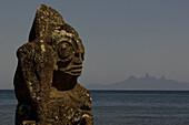 Tiki, weathered stone figure in front of Ua Pou island, Marquesas, Polynesia, Oceania