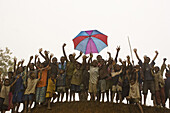 A group of cheering children with umbrella, Langila, Papua New Guinea, Oceania