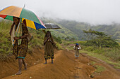 Women walking with umbrella on track, Langila, Highland, Papua New Guinea, Oceania