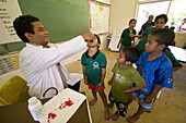 Doctor giving vitamins to pupils at school, Pohnpei, Micronesia, Oceania