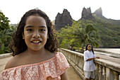 Two girls in front of peaks at Hatiheu, Nuku Hiva, Marquesas, Polynesia, Oceania