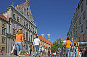 People going shopping at the pedestrian area Neuhauser Strasse with the facade of St. Michael, the towers of Frauenkirche in the background, Munich, Bavaria, Germany