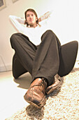 Selective focus on shoes, man sitting on chair with arms behind his head