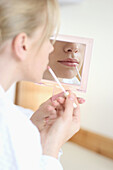 Close up shot of mouth of a girl putting lipstick on in a mirror