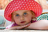 Beautiful 3 year old girl with huge blue eyes, smiling into camera, wearing a massive sunhat