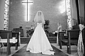 Braut, Bräute, Brautkleid, Brautkleider, Ehe, Eine Person, Eins, Eintreten, Elegant, Eleganz, Erwachsene, Erwachsener, Frau, Frauen, Ganzkörper, Ganzkörperaufnahme, Hochzeit, Hochzeiten, Horizontal, Innen, Kirche, Kirchen, Lifestyle, Mensch, Menschen, Mo