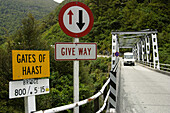 Caravan on one-lane bridge over Gates of Haast, right of way sign, yield . Haast Pass. New Zealand