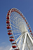LAKEFRONT. Chicago, Illinois. Navy Pier, popular tourist destination, Ferris wheel against blue sky, white with red gondola cars