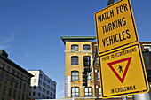 Massachusetts, Boston, Watch for Turning Vehicles sign, yield to pedestrians sign posted on street post in Seaport District