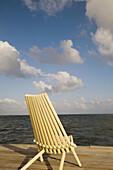 BELIZE Ambergris Caye Slatted yellow wooden chair sit at end of wooden dock, partly cloudy skies, Caribbean waters to horizon