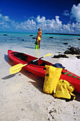 Woman with kayak at edge of lagoon. Aitutaki. Cook Islands
