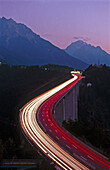 Light tracks at the Europa bridge from traffic as they travel through the Alps along Brenner Pass. Tyrol. Brenner Highway. Austria.