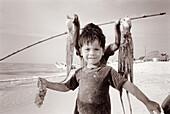 Children with octopuses. Celestun. Yucatan. Mexico